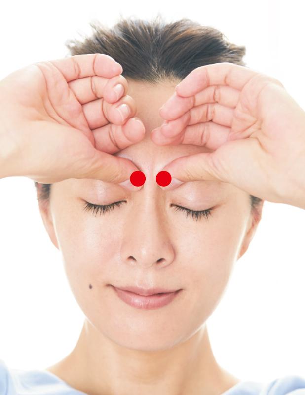 眉頭の少し下を親指で押している女性