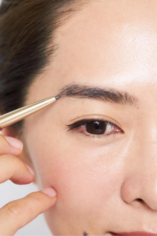 ペンシルで眉毛を描いている女性