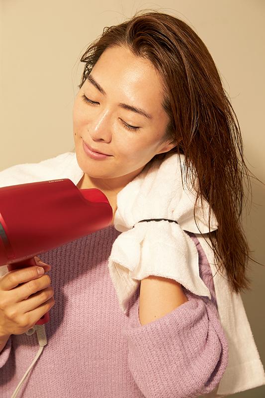 ミトンを手にドライヤーで髪を乾かす女性
