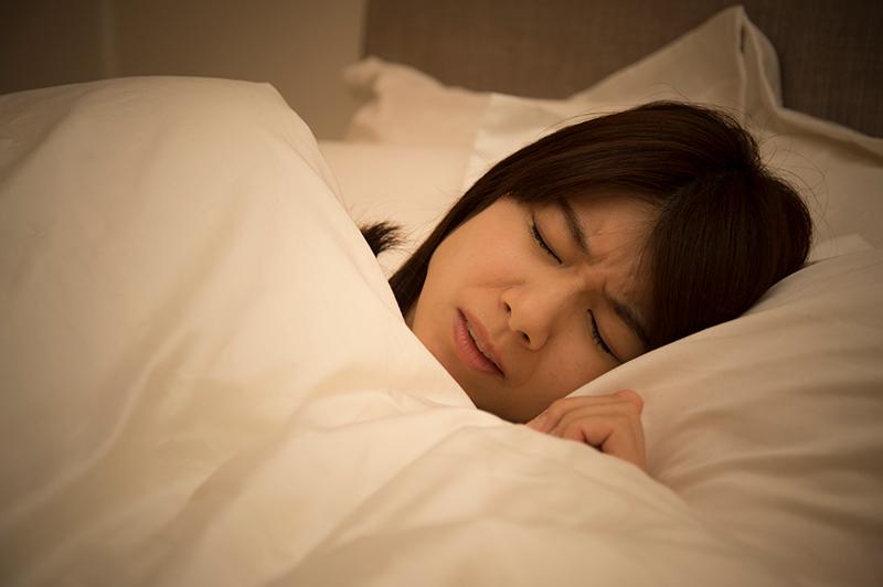 寝苦しそうに布団の中で眠る女性