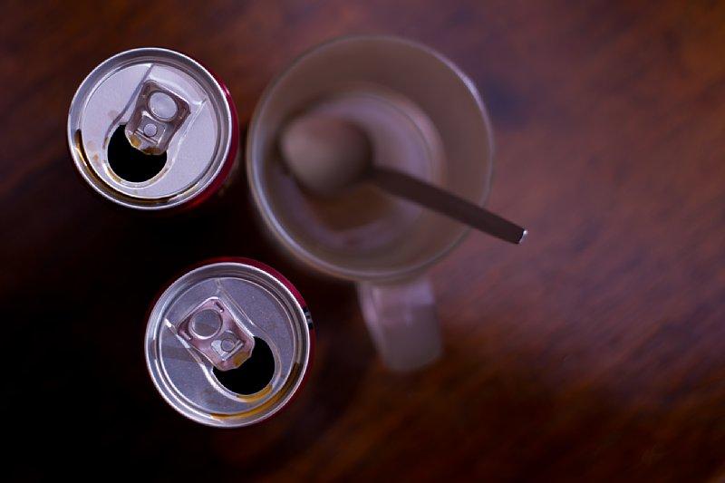 缶コーヒー2つとグラスがテーブルに置かれている