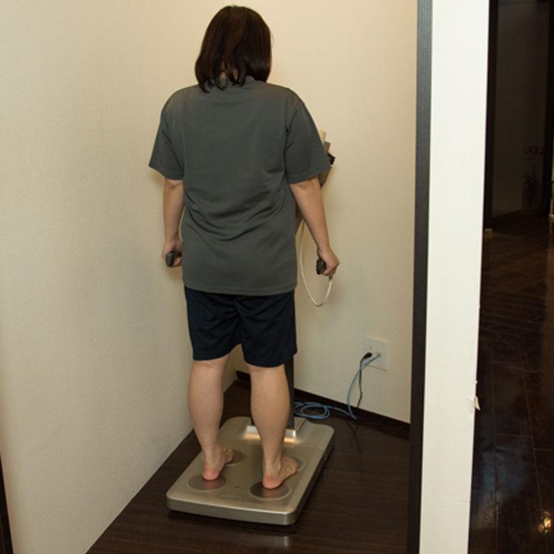 体重計に乗りショックを受けるA子