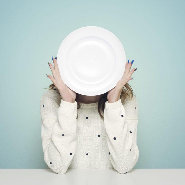 空の皿で顔を隠す女性