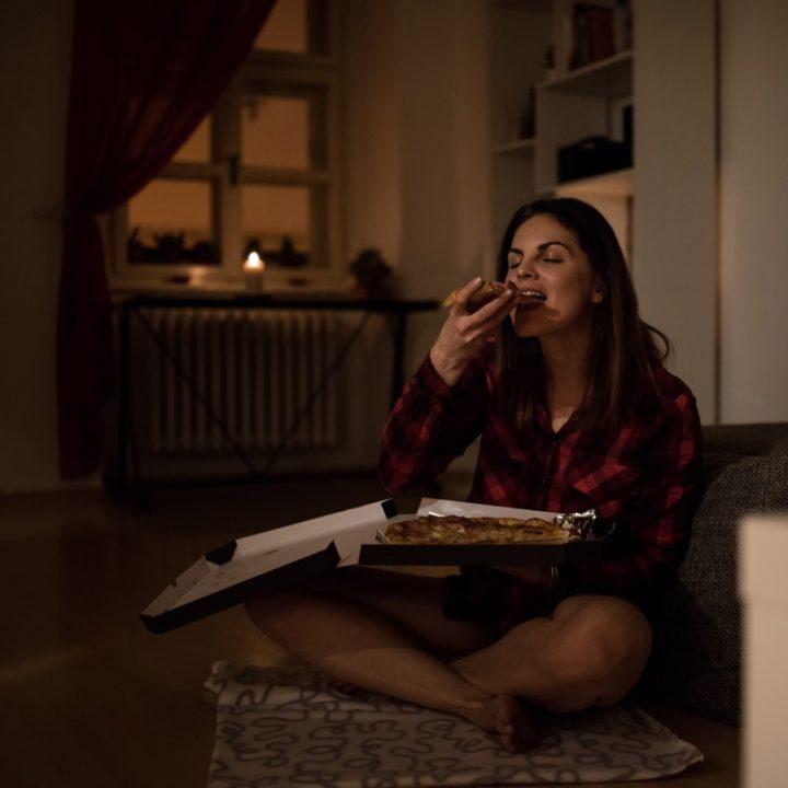 夜中にピザを食べる女性