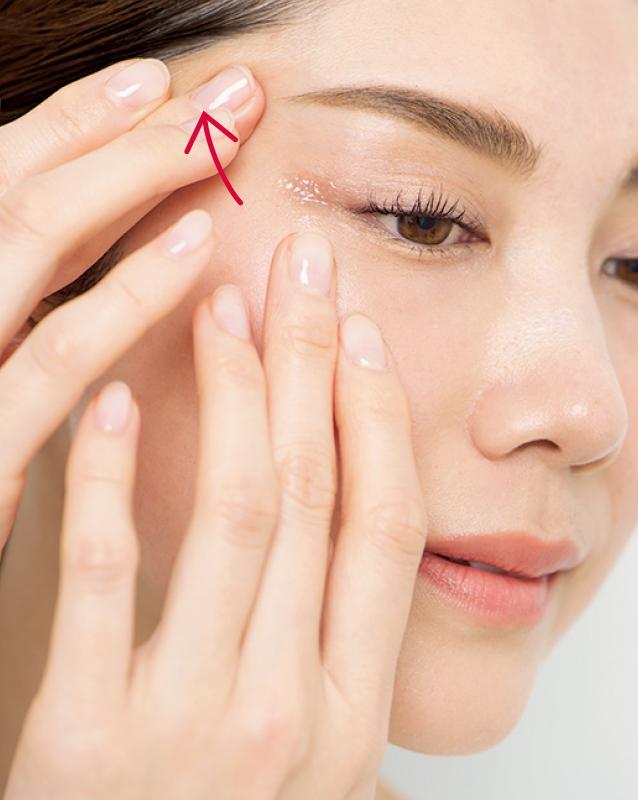 目尻を引き上げるように美容液を塗る女性の顔アップ写真