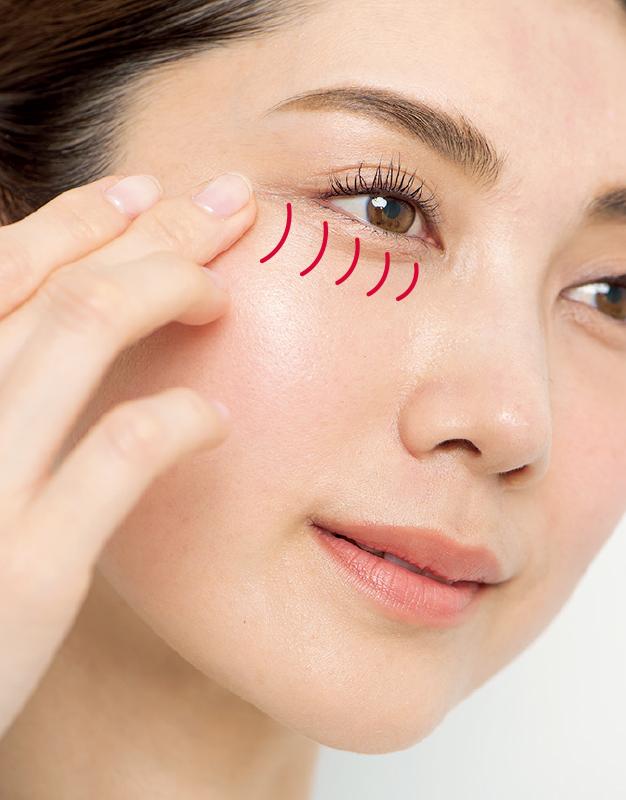目の下に美容液を縦に塗る女性のアップ写真