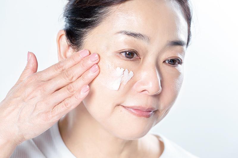 バームを頬にのせている女性