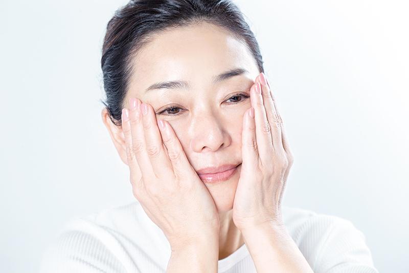 両手のひらで顔を包み込むようにしている女性