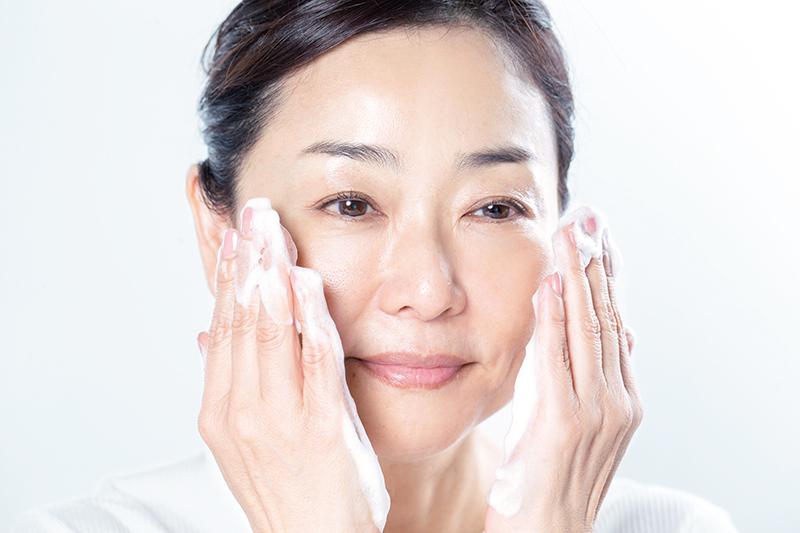 両手のひらに泡をつけて顔を洗っている女性