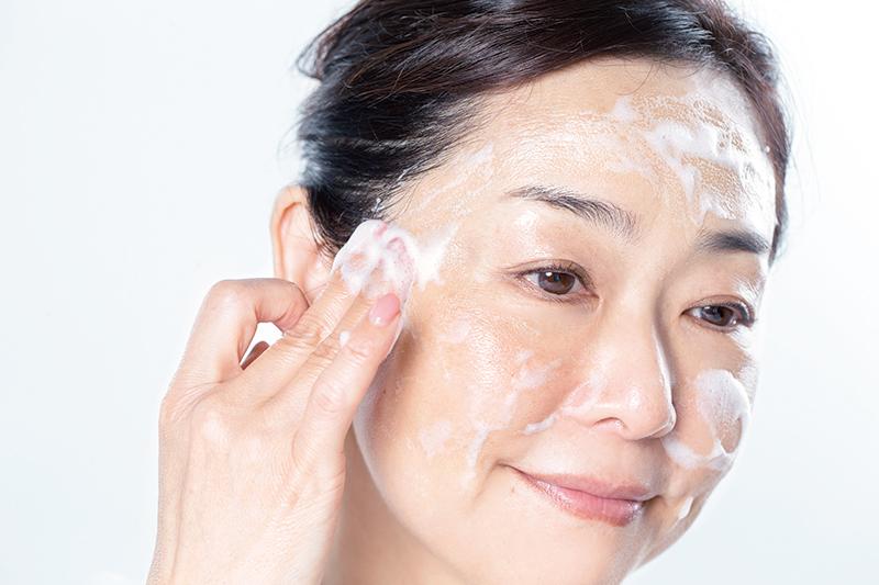 髪の生え際を指先で洗っている女性