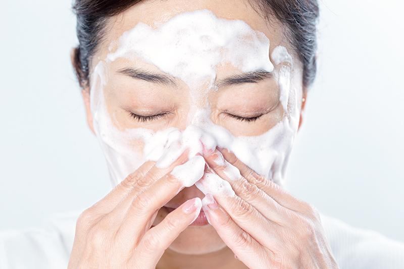 洗顔料の泡を顔全体にひろげている女性