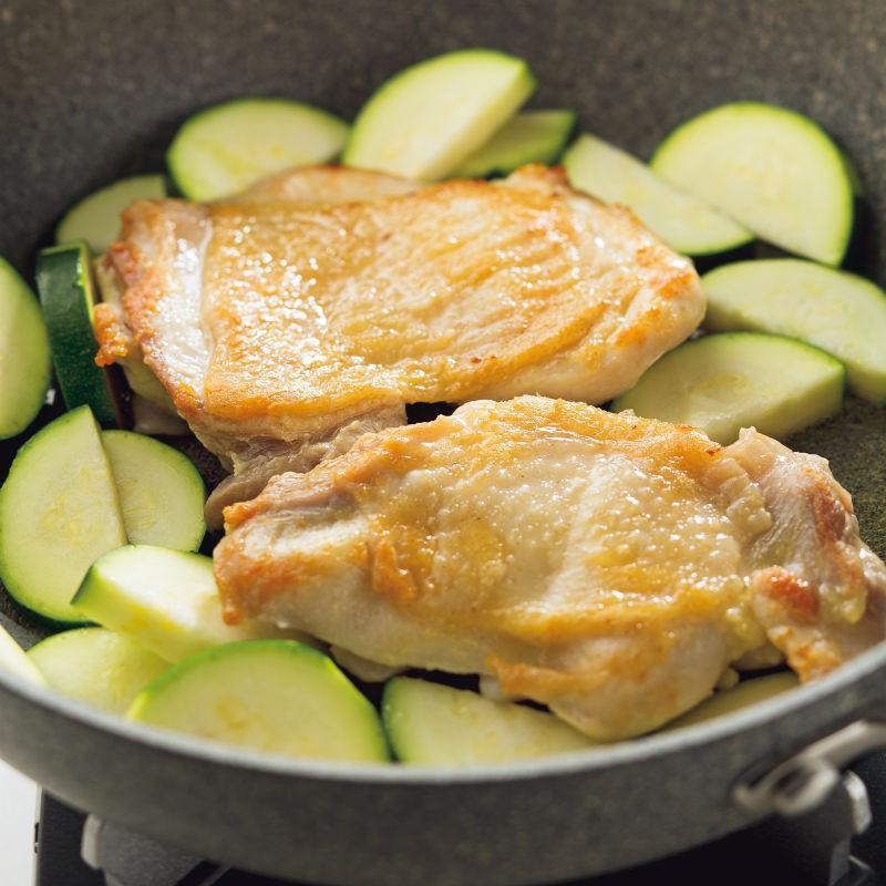 鶏肉とズッキーニをフライパンで調理している