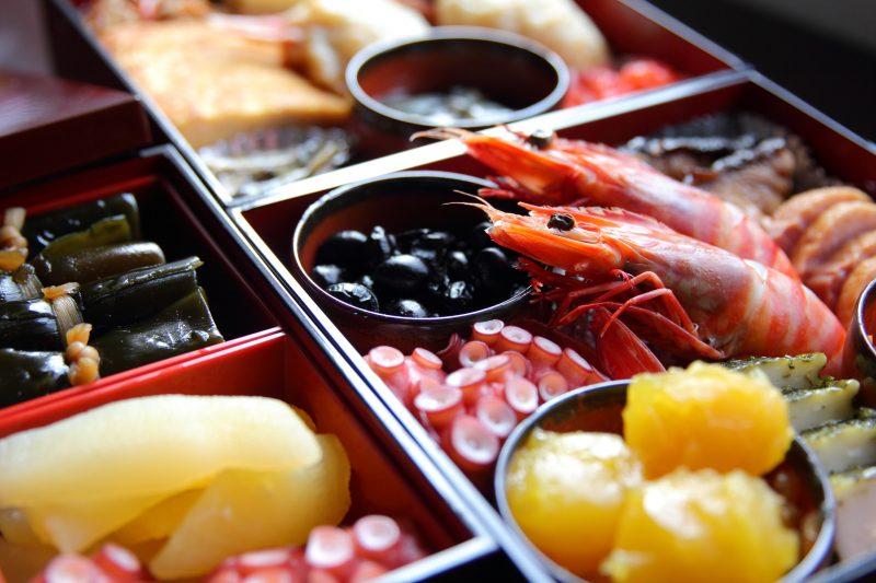 栗きんとんや煮豆などお重に入ったおせち料理が並んでいる