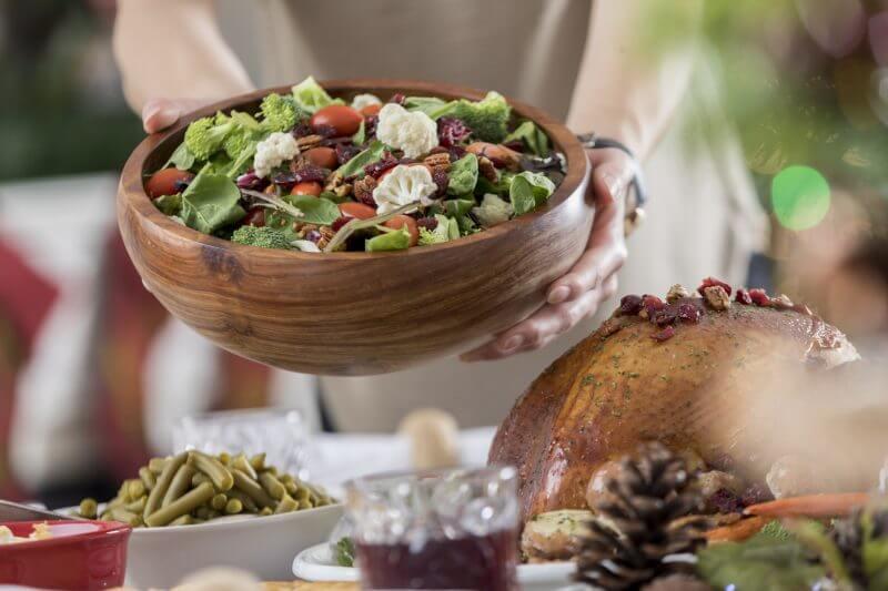 クリスマスの飾りつけがされたテーブルにサラダがボウルいっぱいに入って届けられている