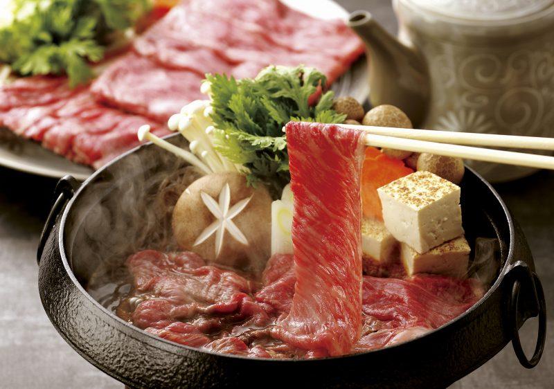すき焼き鍋に、霜降り和牛を箸で入れている様子