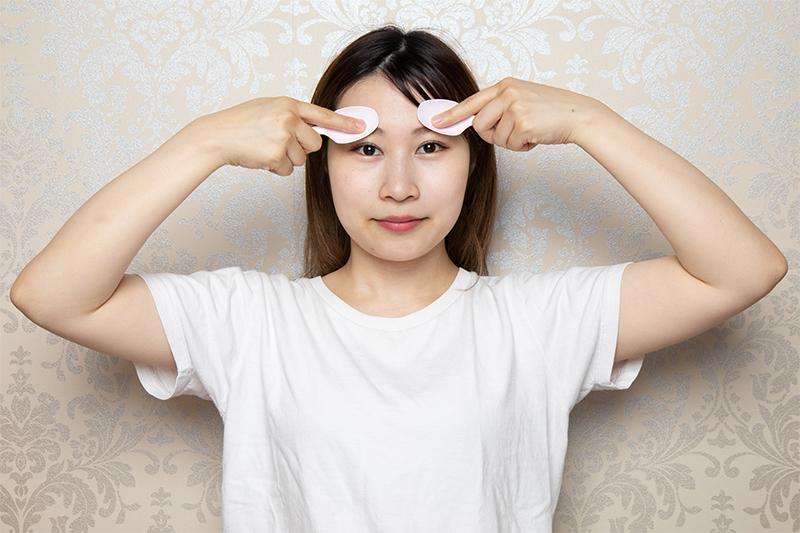 スプーンを両手に1本ずつ持ち、両眉毛をスプーンの腹で押している女性