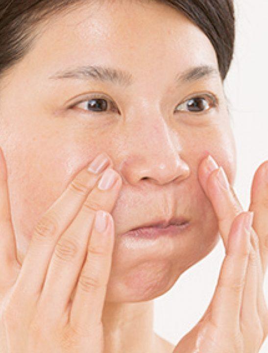 頬をふくらませて化粧水をしみ込ませる女性の顔