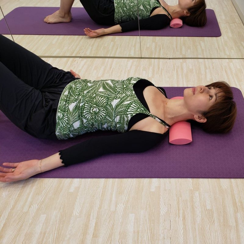 re frame conditioning academyのちょいサポという運動ツールを首の下に入れてエクササイズしている女性