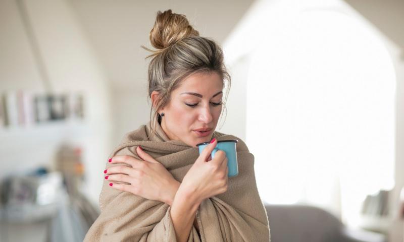 布に包まって飲み物を飲む女性