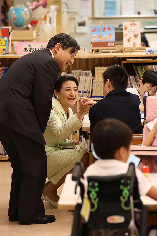 重症心身障害者施設の入居者の方とひざを折り、手を取りながら目線を合わせてお話をされる天皇陛下と皇后雅子さま