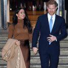 階段を手をつないで降りるヘンリー王子とメーガン妃