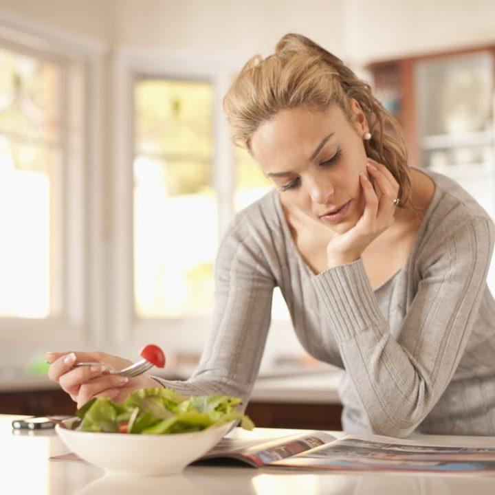 サラダを食べながら本を読む女性
