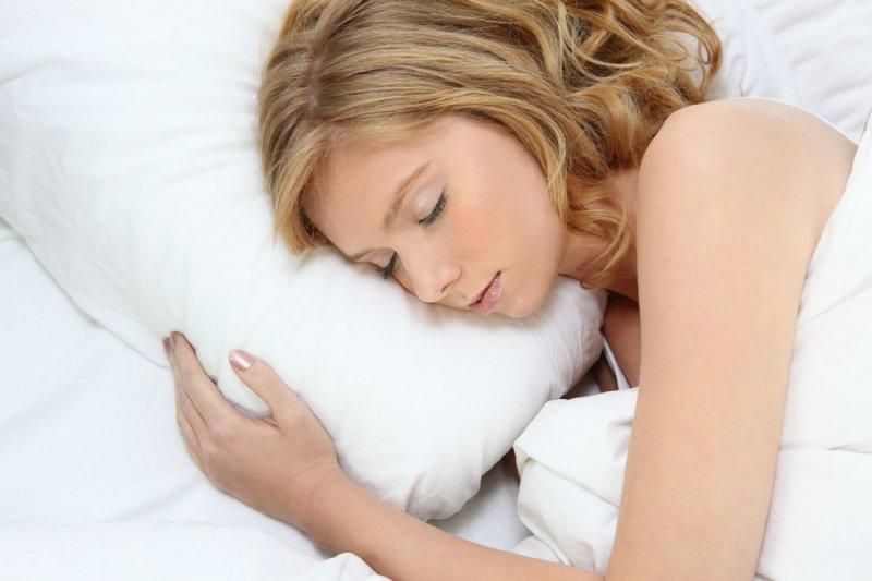 枕に手を添え眠る外国人女性