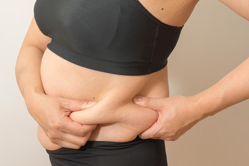 お腹にたまった脂肪を両手でつまんでいる女性