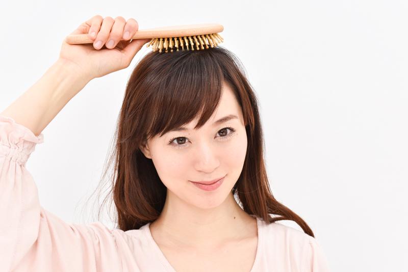 ブラシを使って頭皮をマッサージしている女性