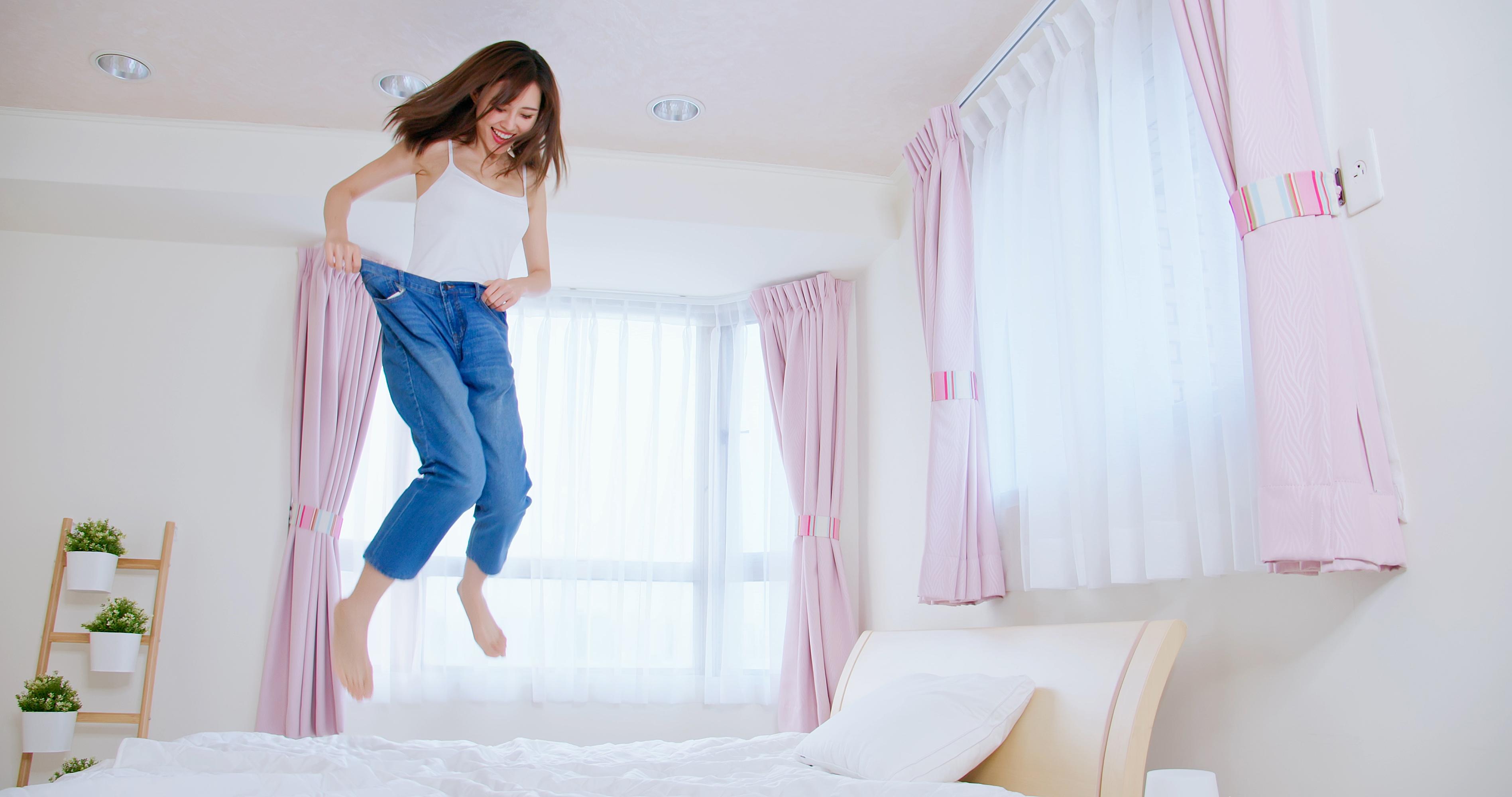 お腹がやせてベッドで飛び跳ねる女性