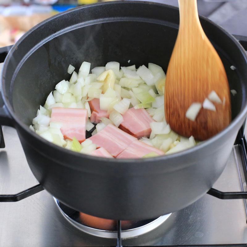 ベーコンと玉ねぎを鍋で炒めている