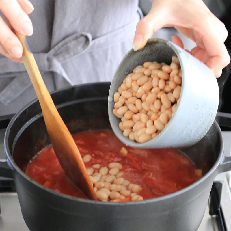 白いんげん豆を煮込んだ鍋に入れている