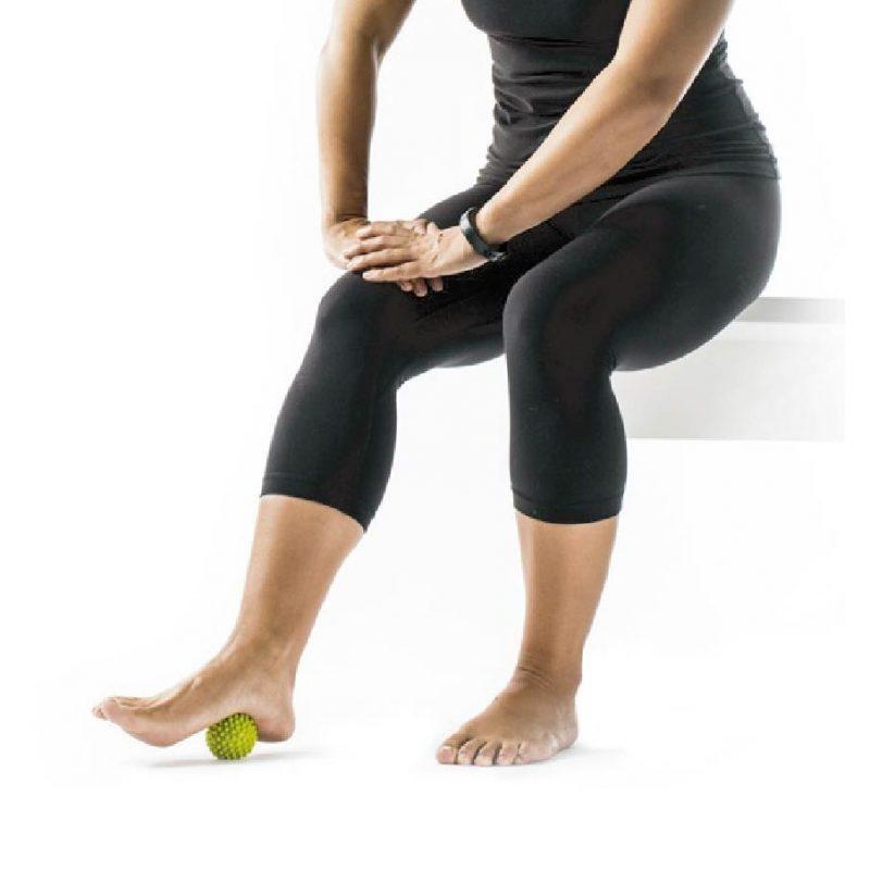 モビポイント マッサージボールを床に置き、足をのせて転がしている女性
