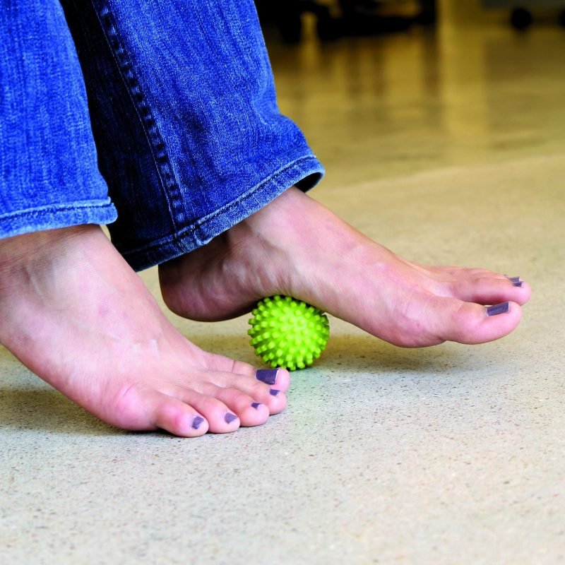 モビポイント マッサージボールを床に置き足の裏で転がしている女性の足元