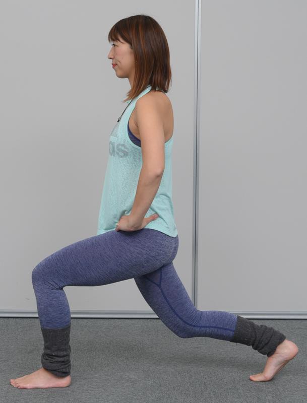 腰を落としてアキレス腱伸ばしをする女性