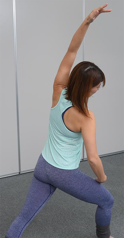 左足を左斜め前に踏み出して曲げ、右手と右脇を左斜め前に伸ばしたポーズをとる女性の後ろ姿