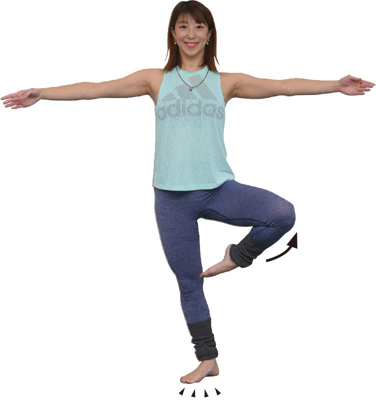 右足で立ち左ももを上げ、両手を横に伸ばした女性