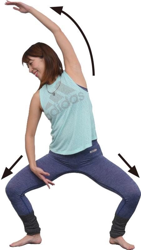 足を大きく開いて腰をまっすぐ落とし、左手を伸ばしながら左脇を伸ばす女性