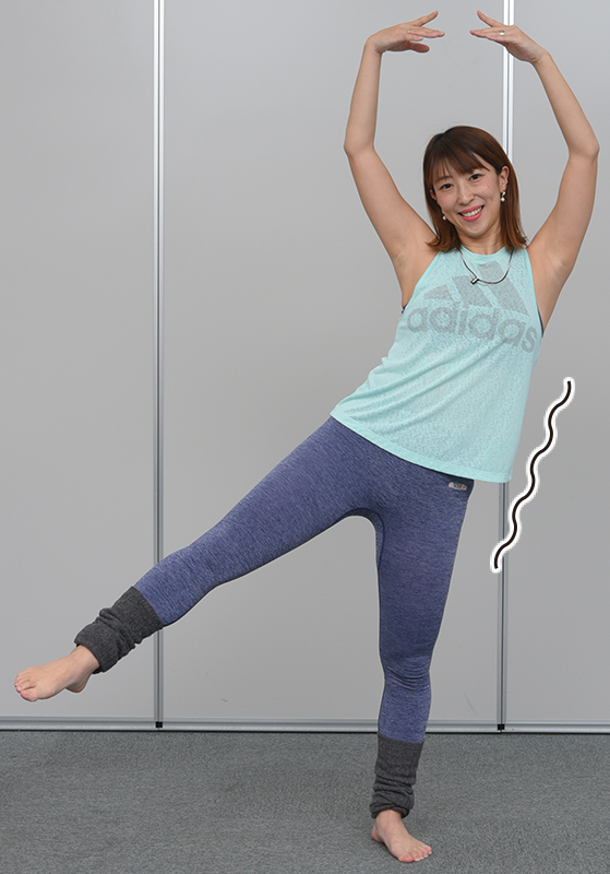 片足立ちで手を上げ、重心側に体が傾いた女性