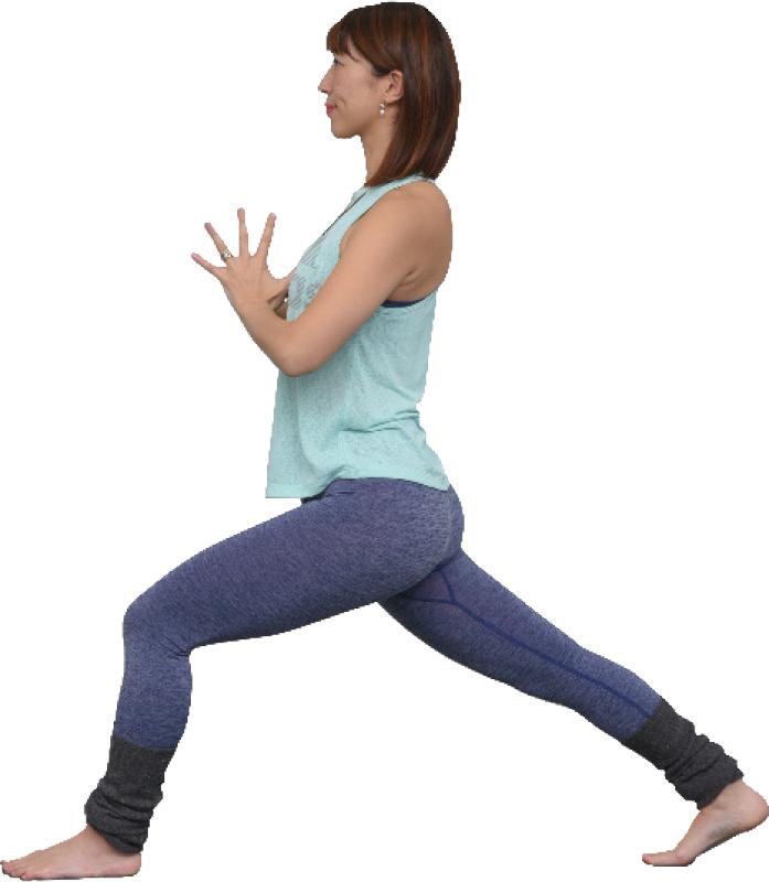 左足を前に出し、右足を後ろに伸ばし、両手を胸の前で合わせた女性