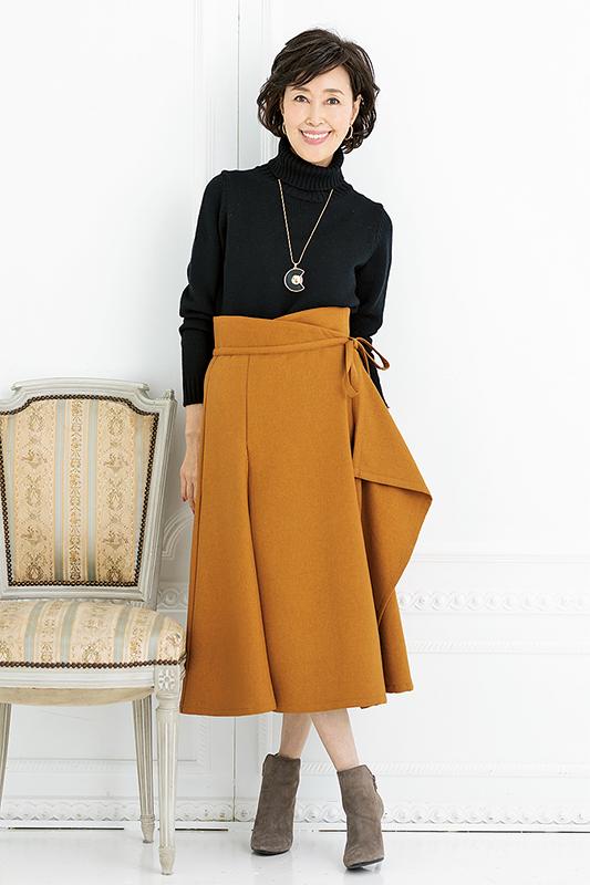 黒のタートルニット、ハイウエストのキャメルの巻きスカート、ショートブーツを合わせた女性の画像