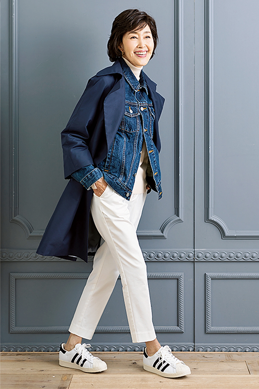 白パンツにスニーカー、Gジャンに紺のコートを着た女性
