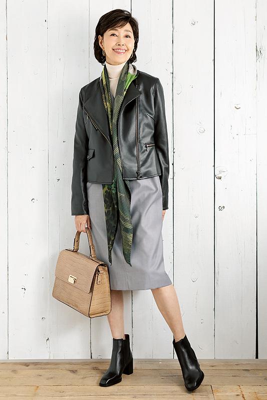 白タートル、ライトグレーの膝丈ワンピースに黒ライダース、スカーフを合わせてバッグを手に持った女性