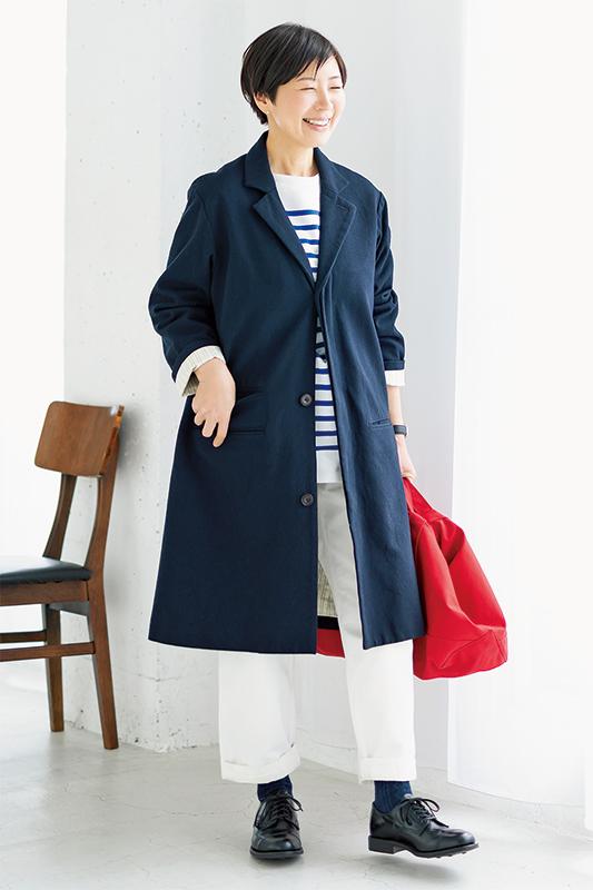 ボーダーカットソーにしろパンツ、紺のコート、赤のバッグを持った女性
