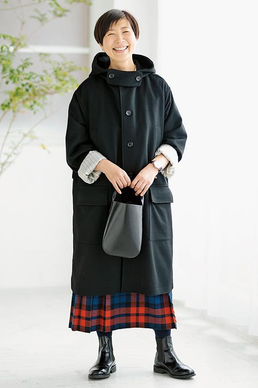 オレンジ黒青のチェックスカートに黒のフードコートを着た女性