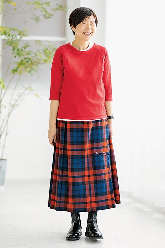 オレンジ青黒のチェックスカートに赤カットソーを着た女性の画像
