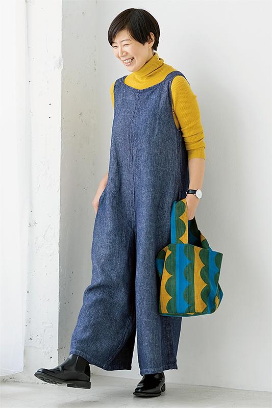 山吹色タートルニットにブルーのサロペットを着た女性