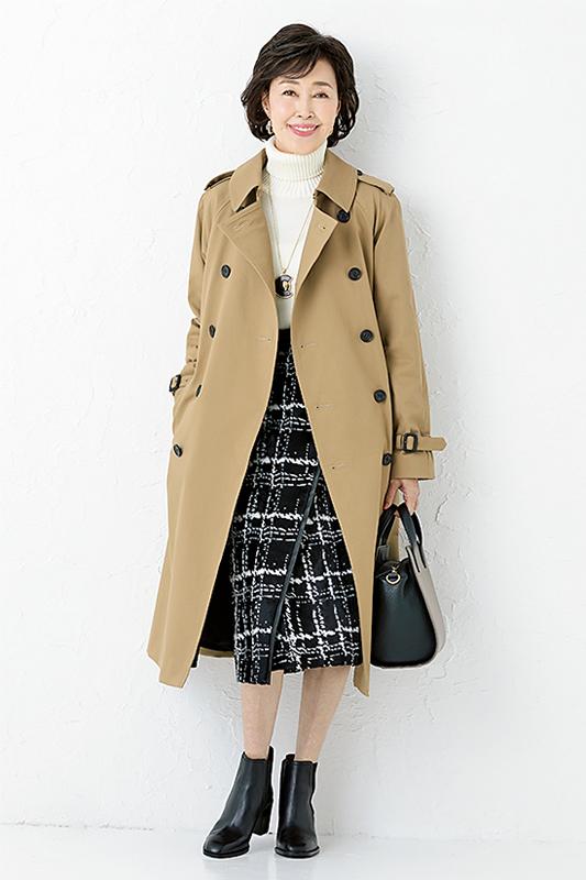 黒のチェックスカートに白ニット、黒のショートブーツ、トレンチを着た女性