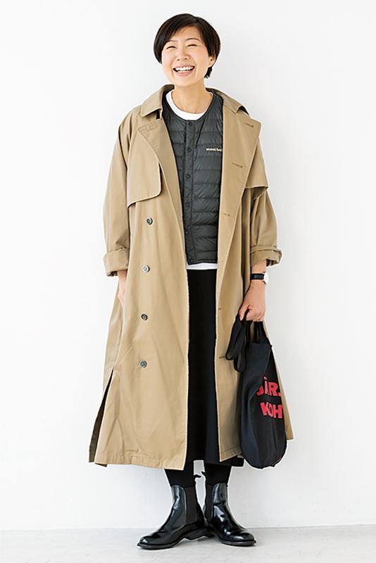 黒スカートに薄手ダウン、トレンチコートに黒エコバッグを持った女性