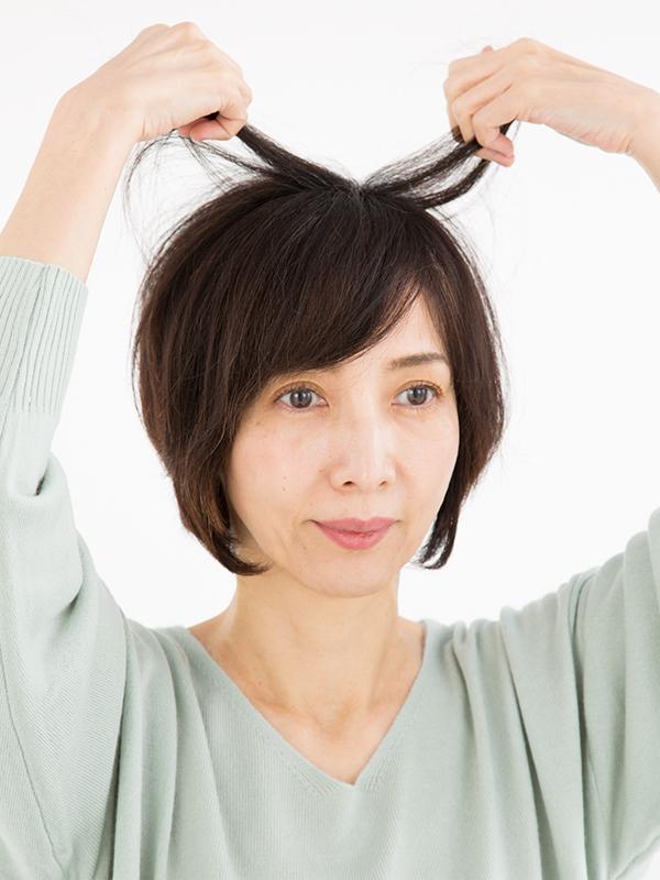 両手でハチ上の髪を持ち上げている女性